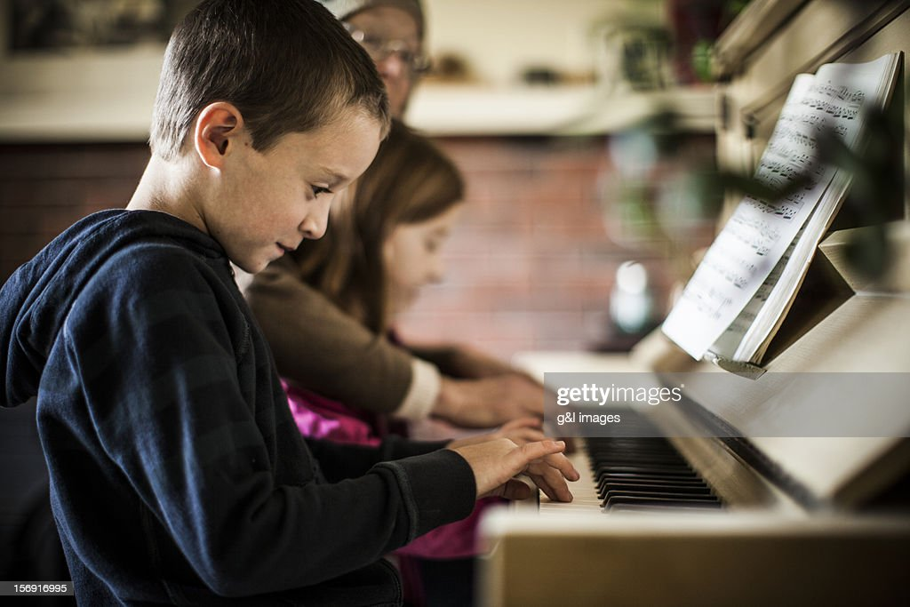 Boy (8yrs) playing piano with sister and mother : Stock Photo
