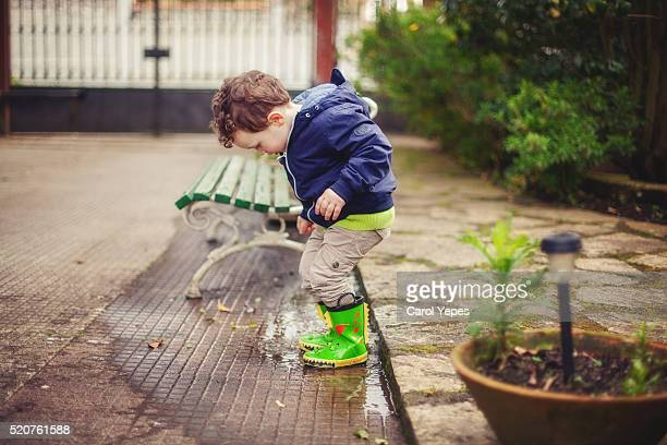 boy playing puddles