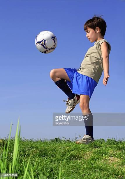 Petit garçon jouant au soccer contre le ciel bleu