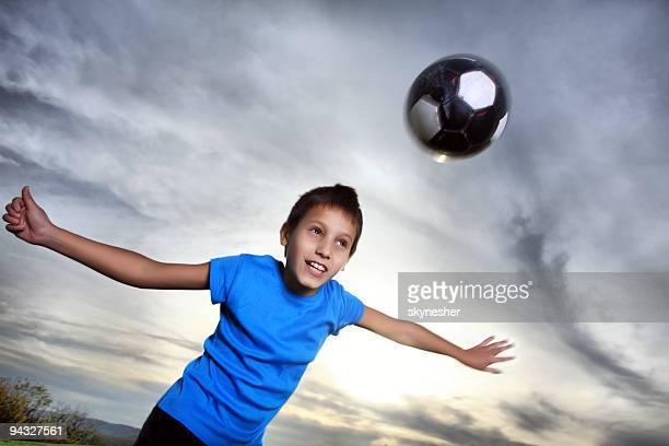 Petit garçon jouant au soccer dans le ciel.