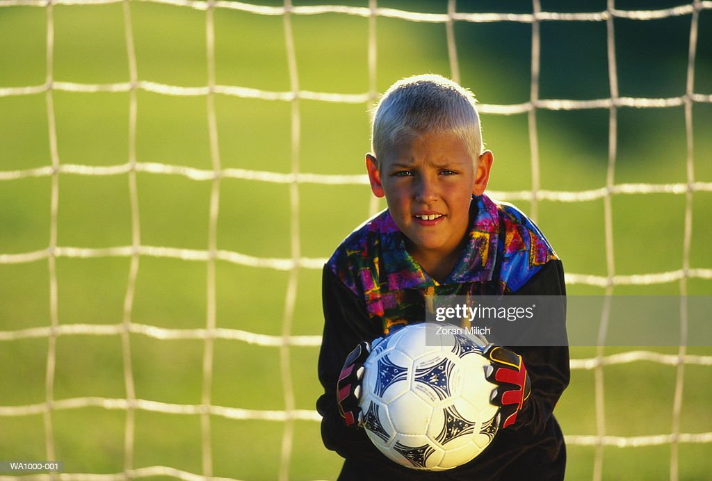 Boy (9-11) playing soccer, holding ball in goal : Stock Photo