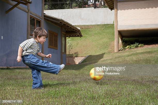 Boy (3-5) playing soccer on lawn, side view