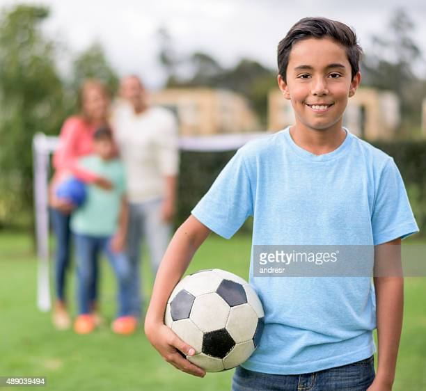 Boy playing soccer with his family