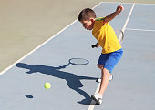 Boy playing tennis in sunny day