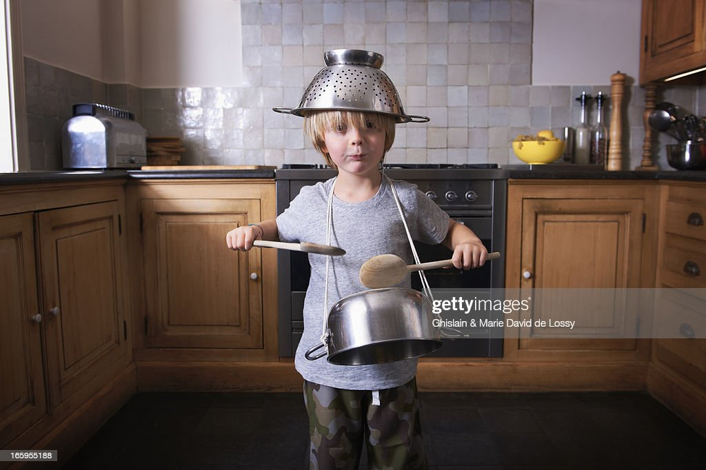 Boy playing the drums on a pan with spatulas : Stock Photo