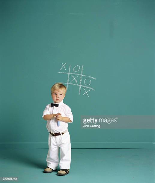 Boy playing tic-tac-toe on wall