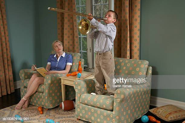 Boy (6-7) playing trombone in living room, mother sitting beside and watching