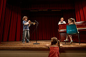 Boy (10-12) playing trumpet on stage, watched by teacher and two girls