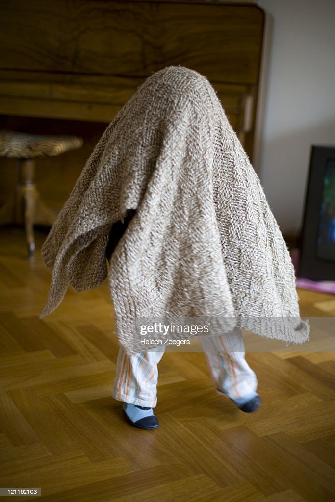 boy playing under knitted blanket ghost dancing : Stock Photo