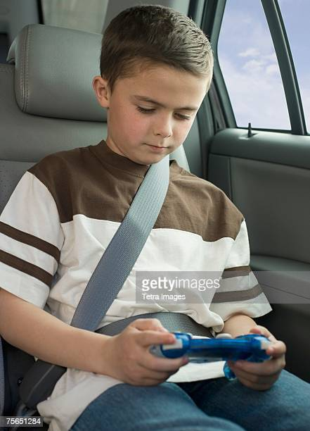 Boy playing video game in car