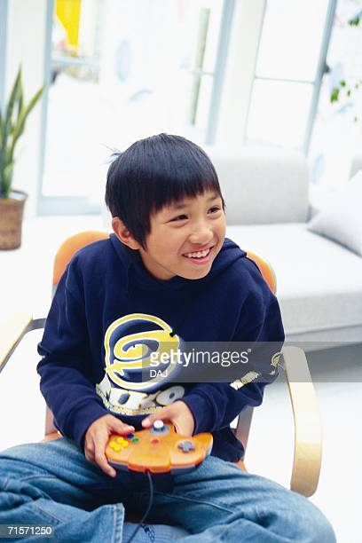 Boy playing video game on a chair with his legs crossed, Smiling, Looking Sideways, High Angle View