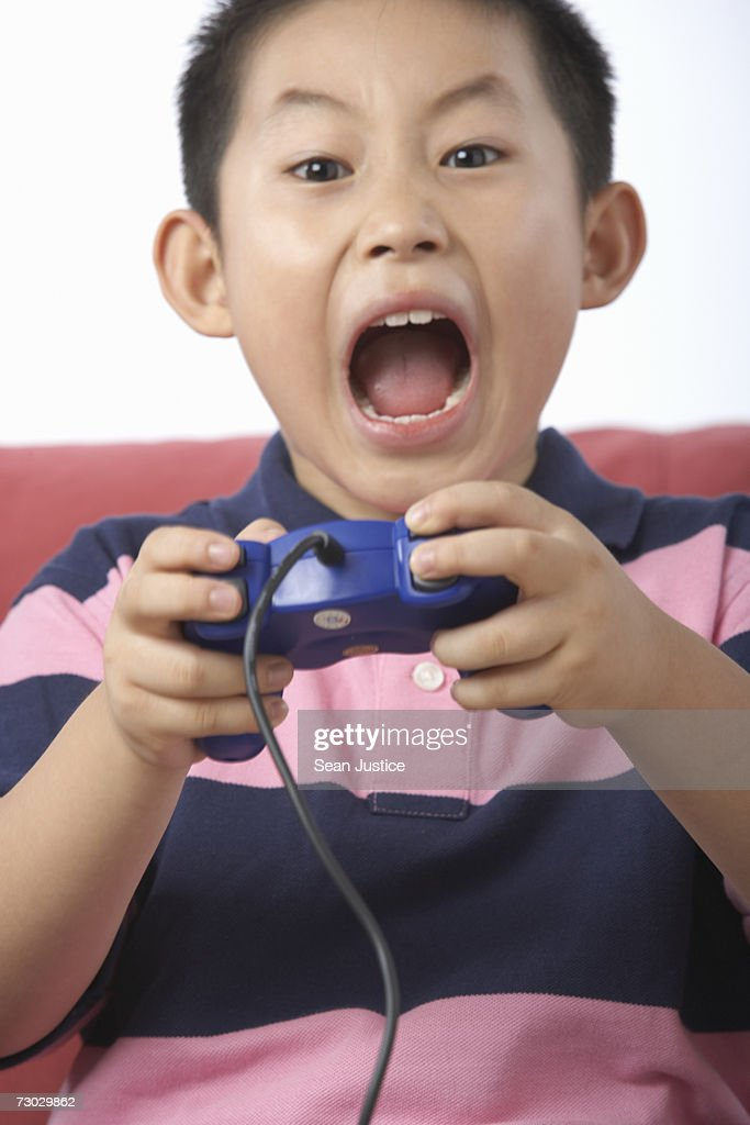 Boy (6-8) playing video game : Stock Photo
