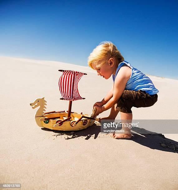 Boy playing viking boat beach