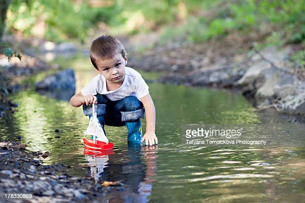 Boy, playing with a boat on a pond