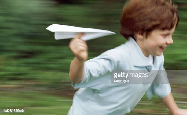 Boy (10-11) playing with a paper plane
