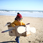A boy playing with a plane on the beach