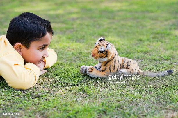 Boy playing with a stuffed toy in a lawn, Gurgaon, Haryana, India