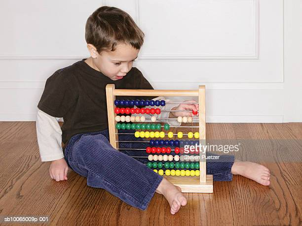Boy (4-5) playing with abacus on ground