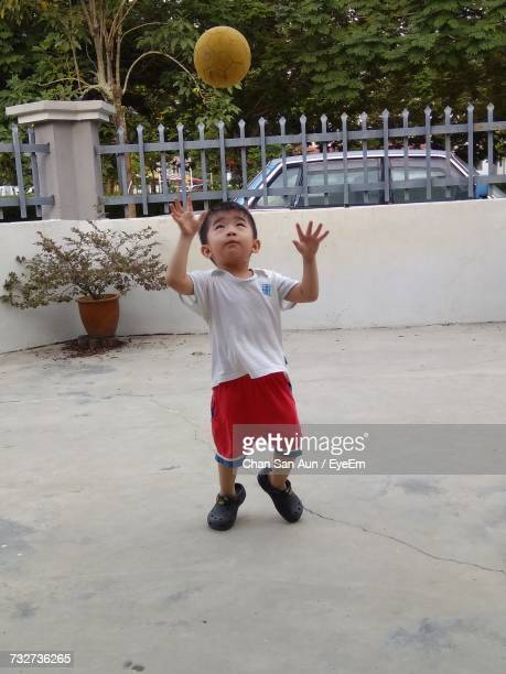 Boy Playing With Ball Against Fence