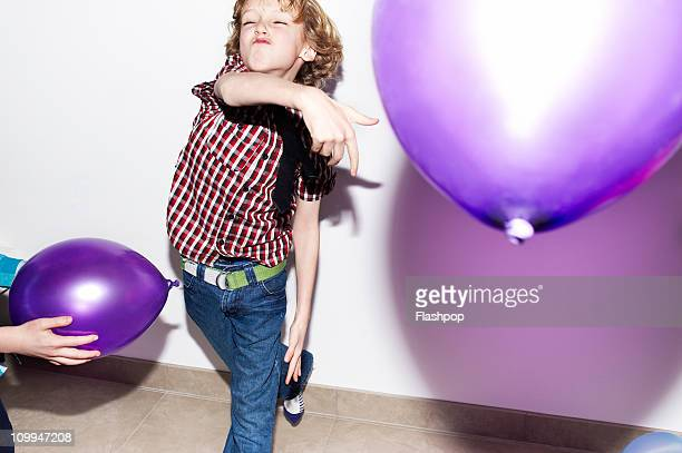 Boy playing with balloons at party