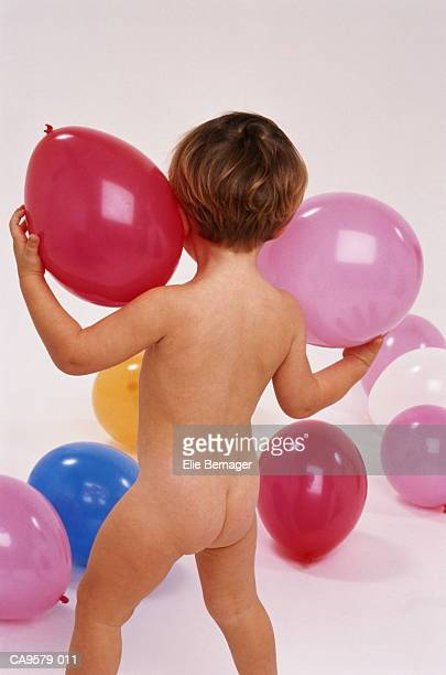 Boy (2-3 years) playing with balloons, rear view, studio shot