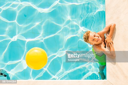 Pool Water With Beach Ball boy playing with beach ball in swimming pool stock photo | getty