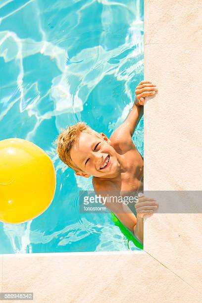 Boy (9 years) playing with beach ball in swimming pool