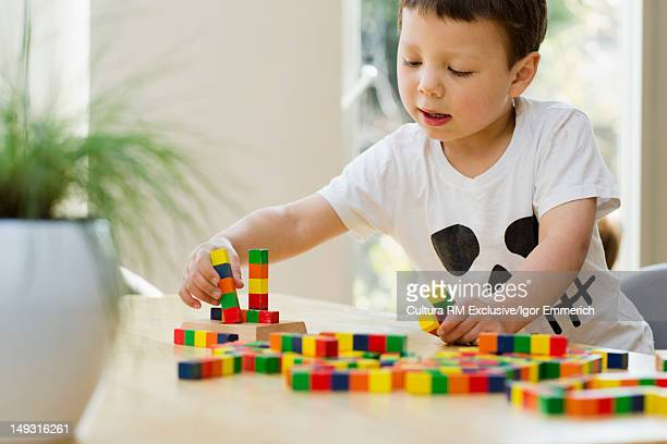 Boy playing with blocks at table