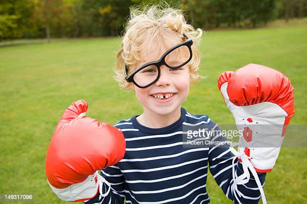 Boy playing with boxing gloves outdoors