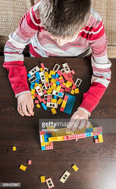 Boy playing with building bricks on a table