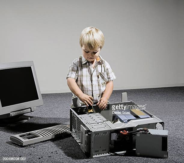 Boy (3-4) playing with computer equipment in studio