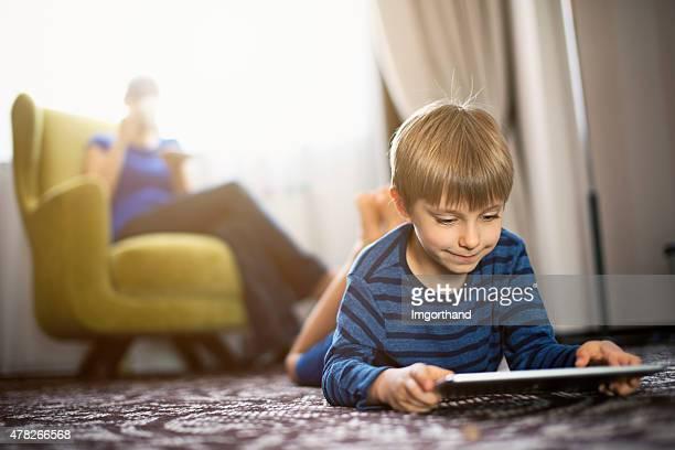 Niño jugando con tableta digital mientras se bebe café de la madre