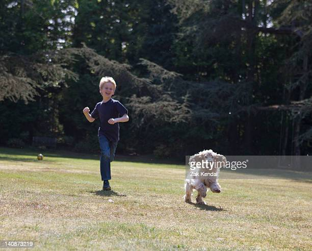 Boy playing with dog in backyard