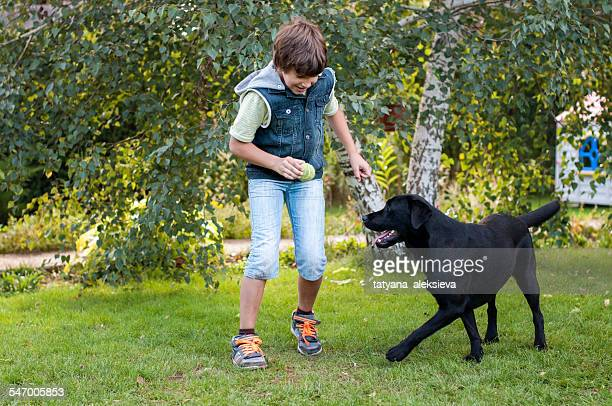 Boy (9-10) playing with dog on lawn