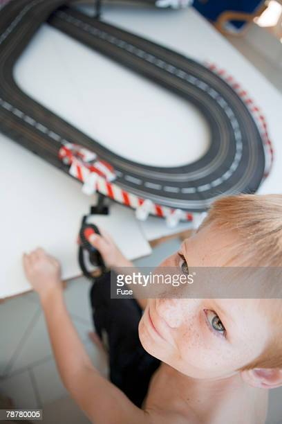 Boy Playing with Electric Car Racing Track
