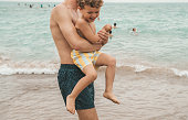 Boy playing with father at the beach