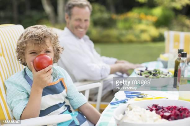 Petit garçon jouant avec repas à table dans le jardin
