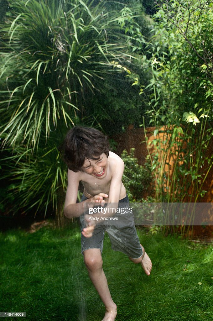 Boy playing with garden water sprinkler spray : Stock Photo