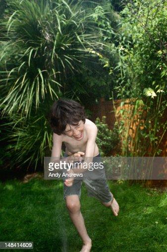 Boy playing with garden water sprinkler spray : Stock Photo