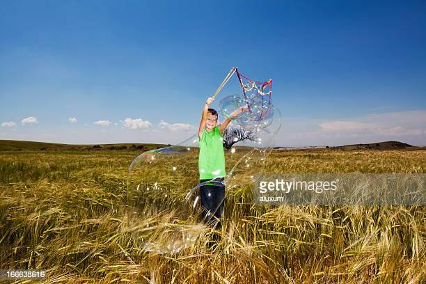 Ragazzo giocando con le bolle di sapone gigante