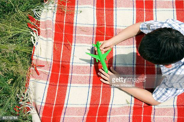Boy playing with green toy plane
