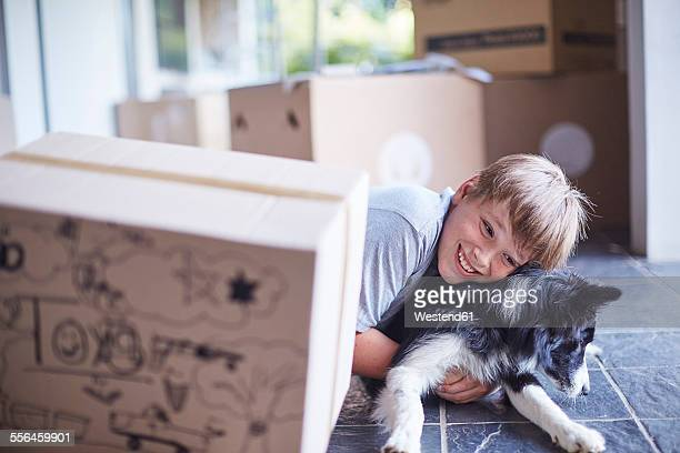 Boy playing with his dog in new home