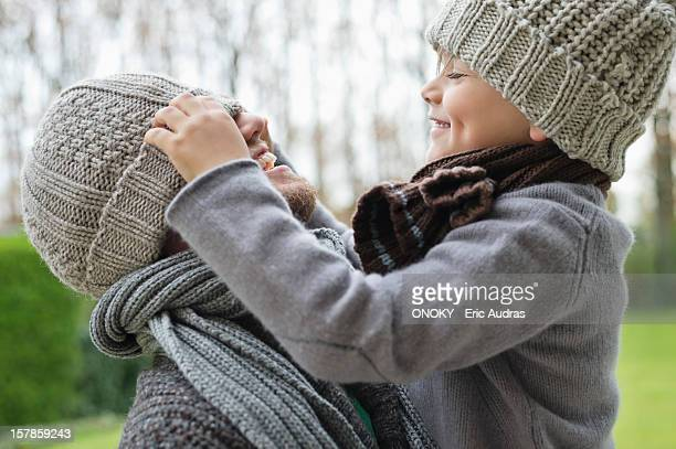 Boy playing with his father's cap