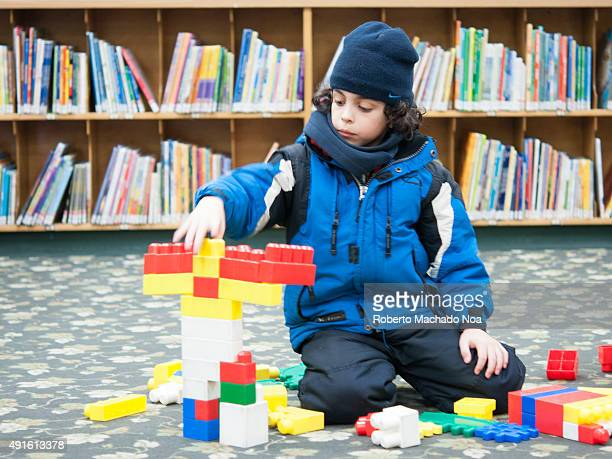 Boy playing with Legos in Toronto Public Library He is wearing a blue jacket and black hat while stacking multicolored blocks on top of each other He...