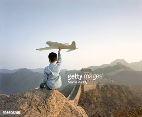 boy playing with model airplane on great wall