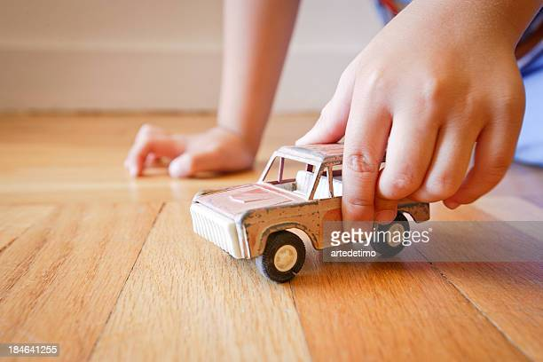 Boy playing with old red toy SUV truck