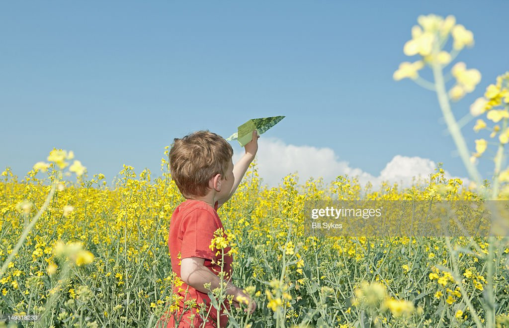 Boy playing with paper airplane in field : Stock Photo