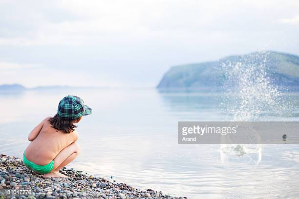 boy playing with pebbles on a beach