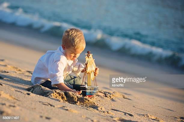 Petit garçon jouant avec bateau Pirate sur la plage