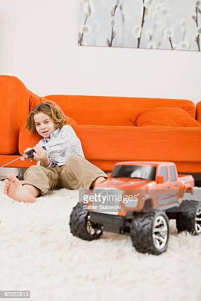 Boy (6-7) playing with remote control car
